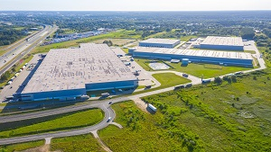 Aerial Top View of Industrial Storage Building Area with Solar Panels on the Roof and Many Trucks Unloading Merchandise.